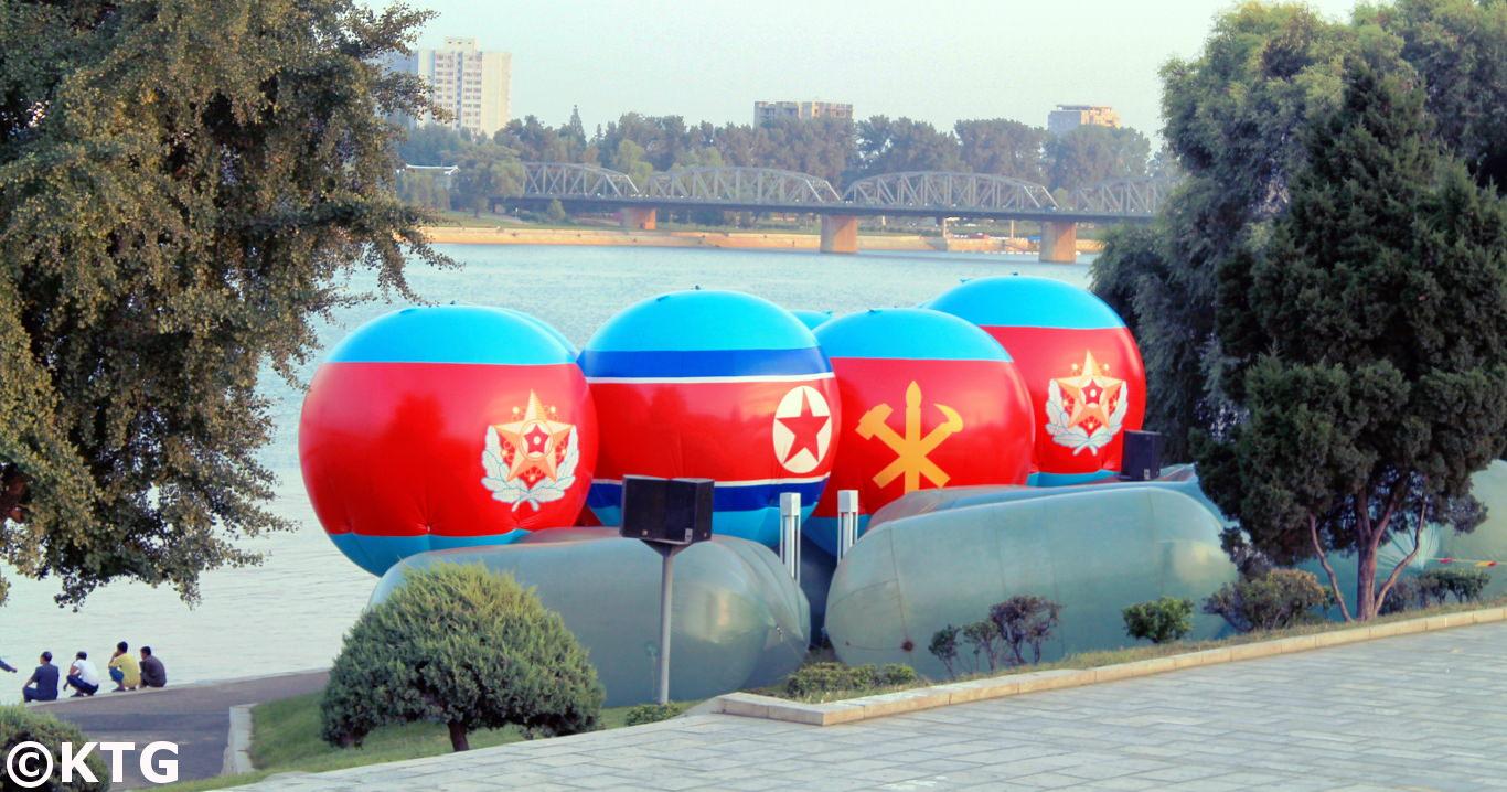 Imagen de la bandera de la RPDC y del símbolo del Partido de los Trabajadores de Corea en el medio de dos emblemas militares de la RPDC
