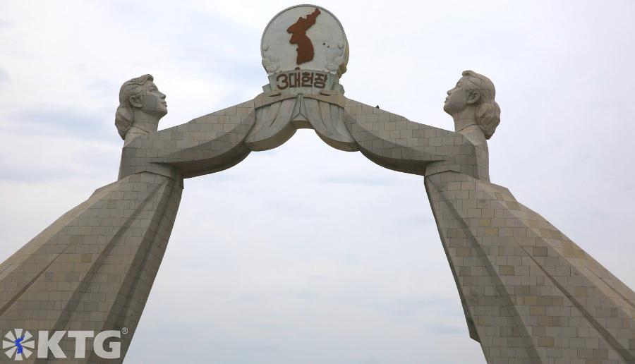 Monumento de granito de dos damas coreanas vestidas con trajes tradicionales coreanos sosteniendo el estandarte de las Tres Cartas para la Reunificación de Corea. El Arco de la Reunificación se encuentra en las afueras de Pyongyang, capital de Corea del Norte, RPDC. Viaje organizado por KTG Tours