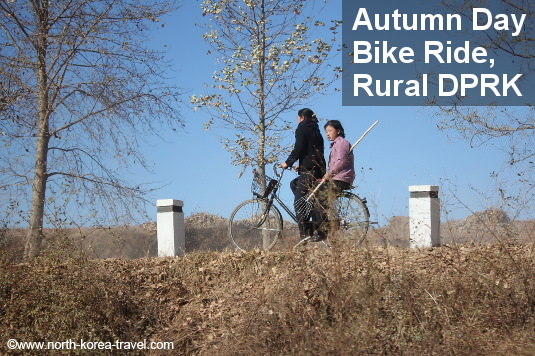 North Koreans ride a bike on an autumn day in the countryside