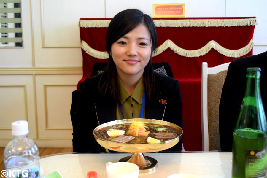 North Korean top guide Kim Sung Mi at the Okryu restaurant ie the Okryu-gwan or okryugwan with a bowl of cold noodles and a bottle of taedonggang beer in the capital of North Korea with KTG Tours