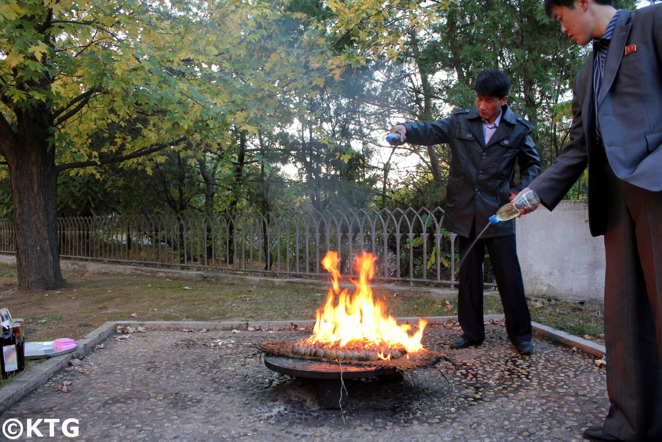 North Korean men pouring petrol over clams in order to prepare a clam barbecue. We can have a gasoline clam BBQ when staying at the Ryonggang Hot Spa Hotel in Onchon county near Nampo city on the west coast of North Korea, DPRK. Trip arranged by KTG Tours