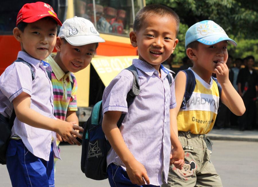 Nyfikna Nordkoreanska barn ler vid åsynen av en västerlänning