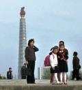 familia bajo la torre juche en Pyongyang