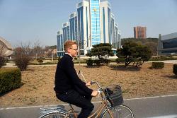 Viajero de KTG Tours en bicicleta por Pyongyang, capital de Corea del Norte