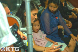 KTG traveller interacting with a North Korean girl in the Pyongyang metro