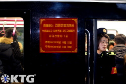 Pyongyang metro staff member. They dress in what looks like navy blue military uniforms