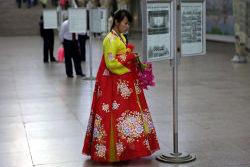 north Korean lady reading the newspaper at the Pyongyang metro in North Korea