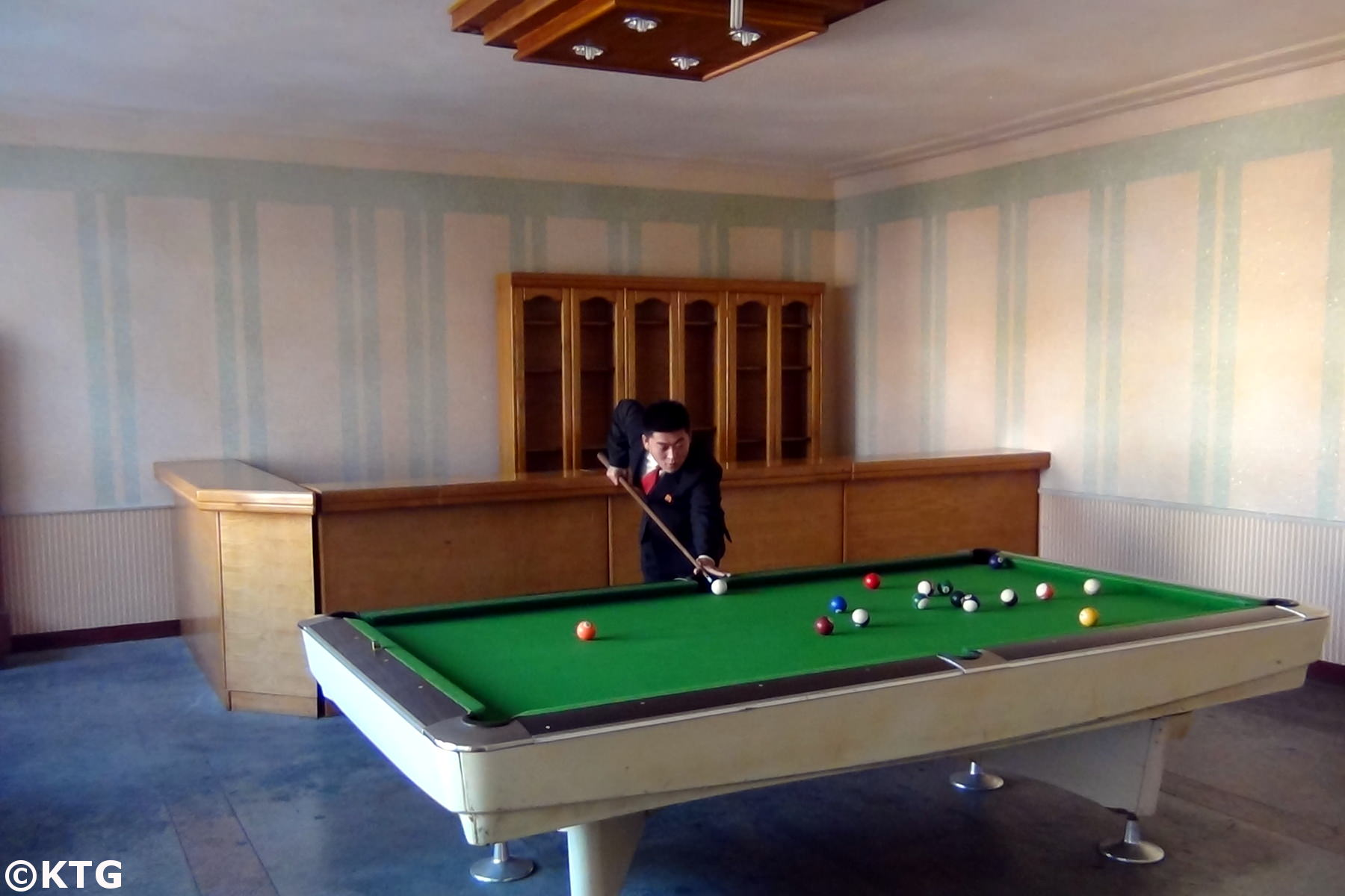 North Korean man playing pool at the Jangsusan Hotel in Pyongsong city, North Korea, DPRK