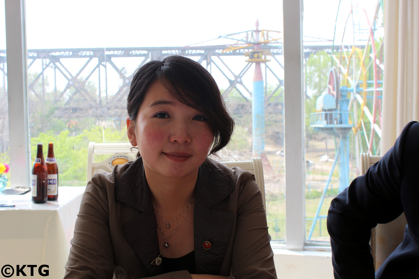 Ms Kim, North Korean guide from Pyongyang having lunch at the Myohyansgan agency restaurant in Sinuiju city in North Korea, DPRK, just across from Dandong in China. The bridge in the background is the friendhsip bridge that connects both countries. Picture taken by KTG Tours