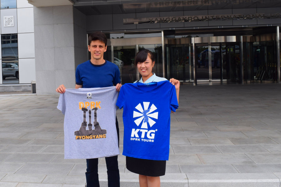 KTG staff member with North Korean guide, posing with KTG t-shirts, at the entrance of the Yanggakdo Hotel in Pyongyang, North Korea (DPRK)