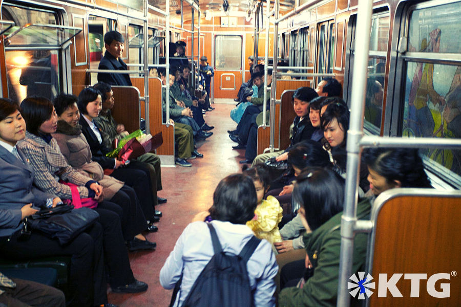 North Korean locals smile in the Pyongyang metro as a KTG tours traveller shows a little girl her camera. Picture of North Korea taken by KTG Tours.