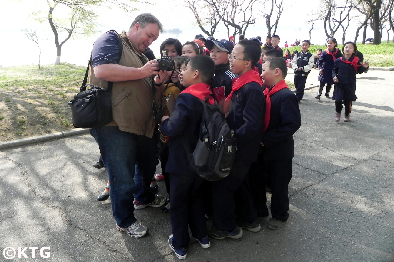 KTG traveller showing North Korean children a picture just taken. This was by the Taedong River in Pyongyang, capital of the DPRK (North Korea). Trip arranged by KTG Tours
