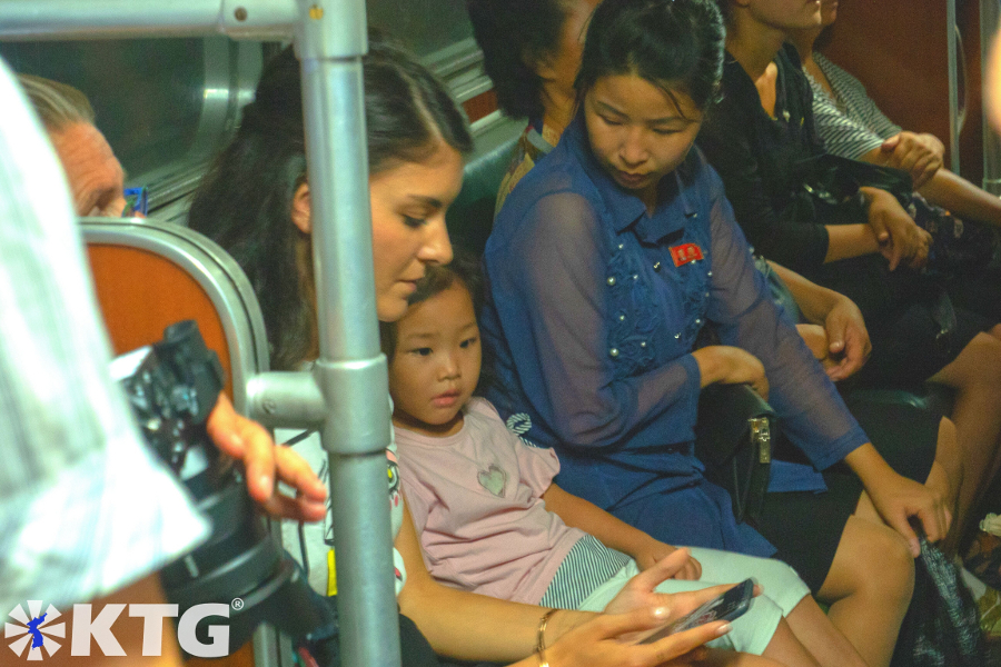 North Korean little girl playing with a traveller from KTG Tours on her mobile phone in the Pyongyang metro, DPRK
