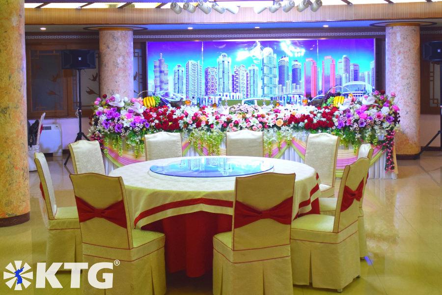 Juego de mesa para un banquete de bodas de Corea del Norte. Puede ver el nuevo horizonte de Pyongyang en la imagen de fondo; Mirae Future Scientists Street, Ryomyong Street y Changjon Street. Este restaurante en el edificio Lotus en la calle Romyong en Pyongyang. ¡Descúbrelo con KTG Tours!