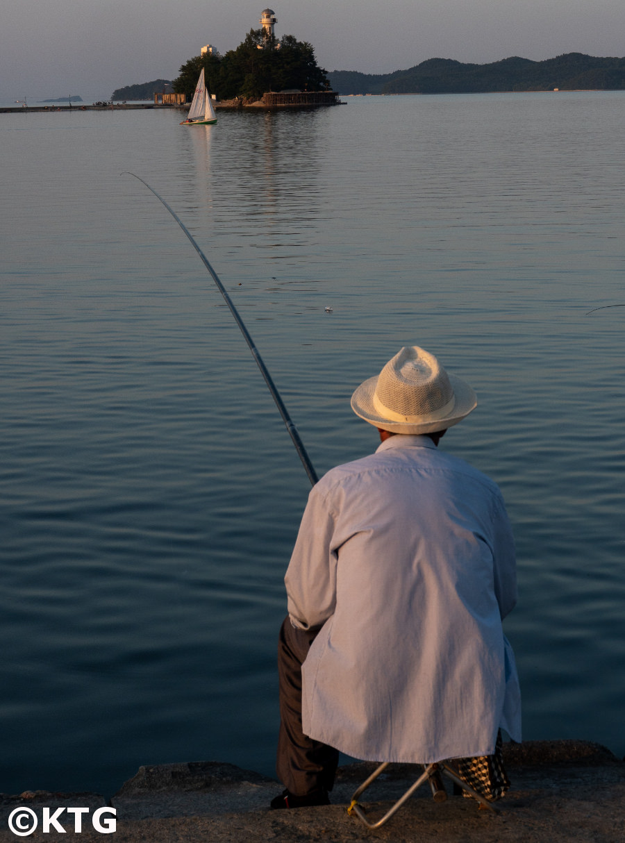Man fishing in Wonsan city, Kangwon province, North Korea (DPRK). You can see the Jangdok islet in the background. Trip arranged by KTG Tours