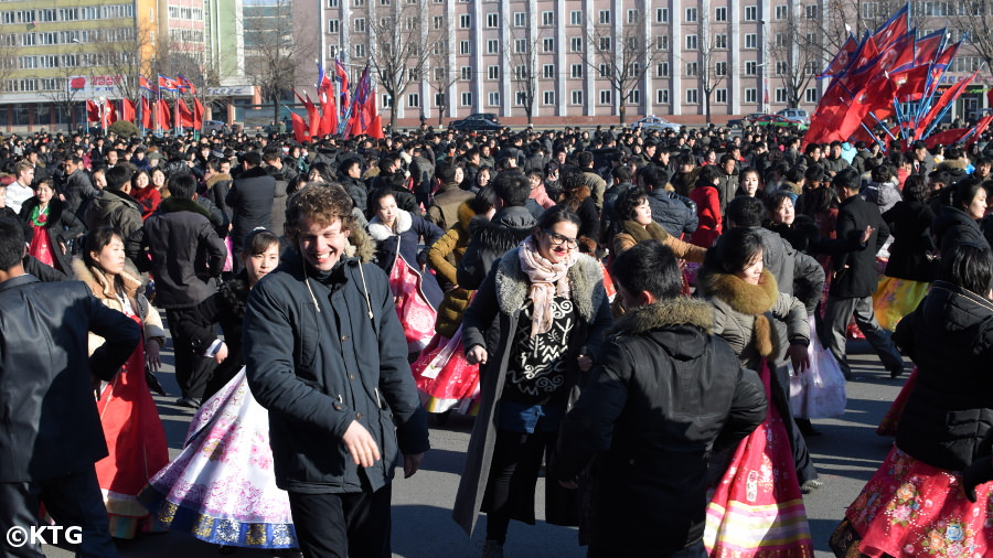KTG staff member dancing with Koreans at the Mass Dances on Leader Kim Jong Il's Birthday in Pyongyang, North Korea (DPRK)