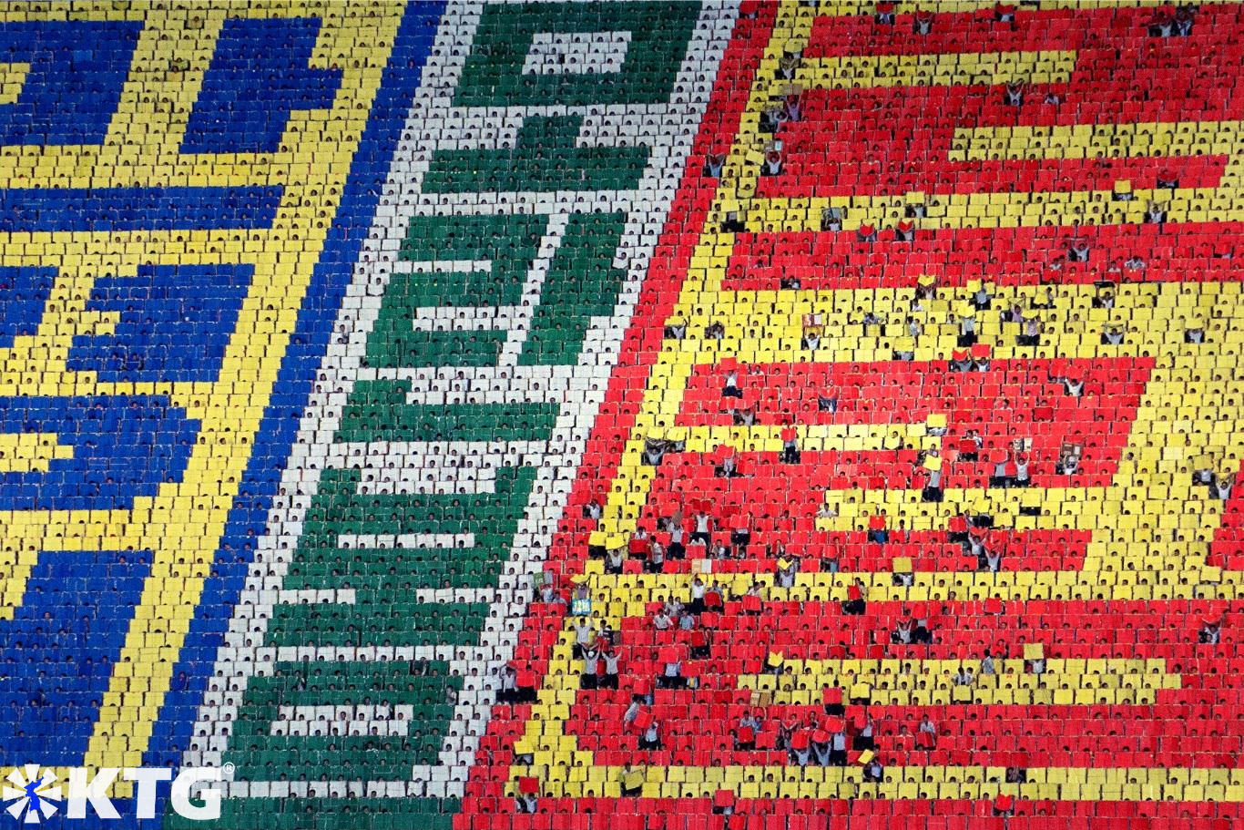 The Mass Games in North Korea have a backdrop of 17,000 students. Each student makes a tiny pixel creating gigantic mosaics. Trip arranged by KTG Travel
