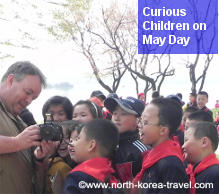 May Day Holiday in North Korea. Some curious North Korean children see pictures taken by a traveller