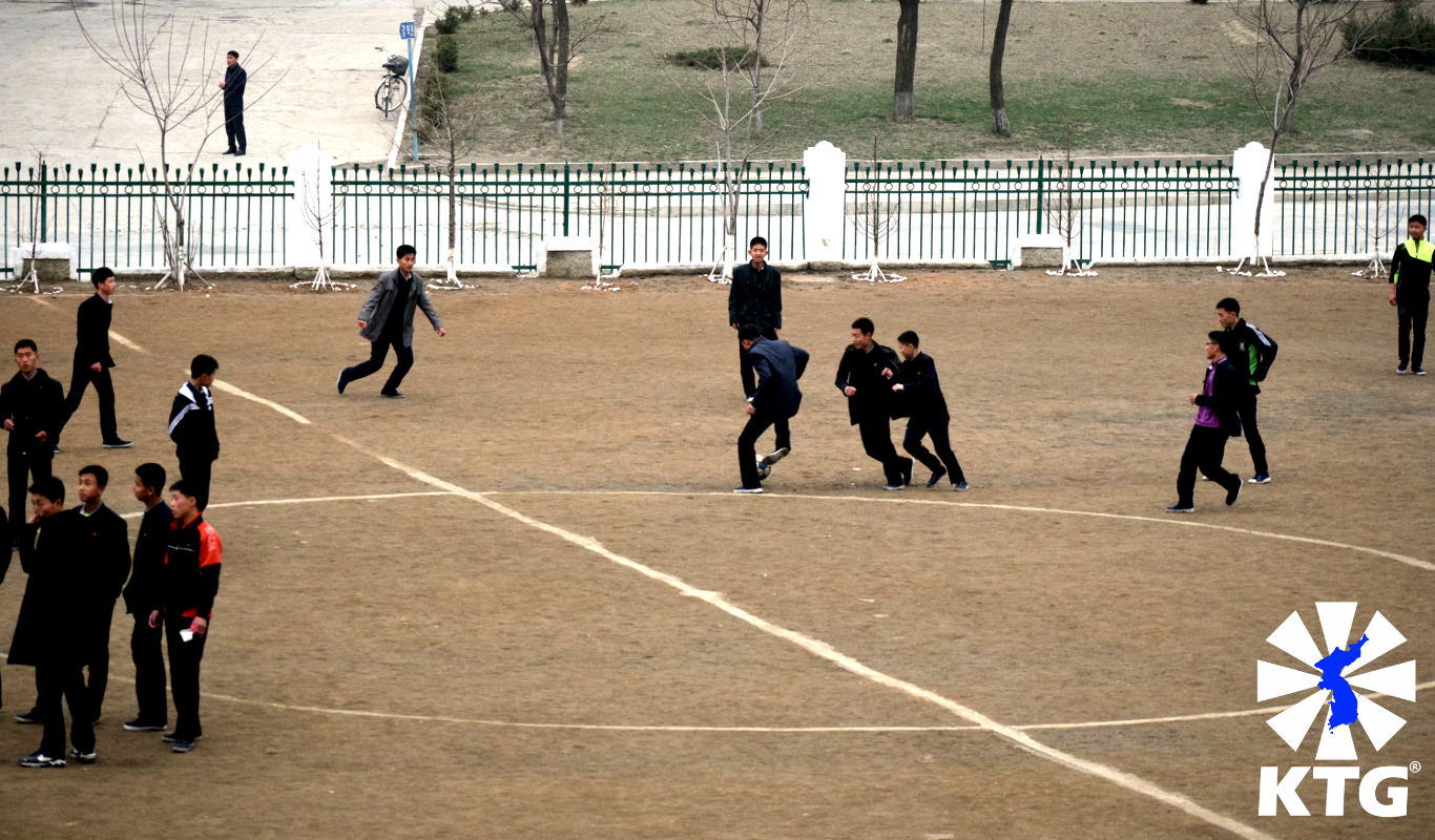 Children playing football (soccer) a middle school playground in Pyongyang, capital of North Korea. Picture taken by KTG Tours