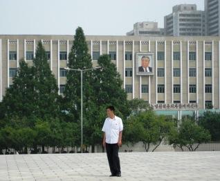 joven en corea del norte con el retrato de Kim Il Sung en el fondo