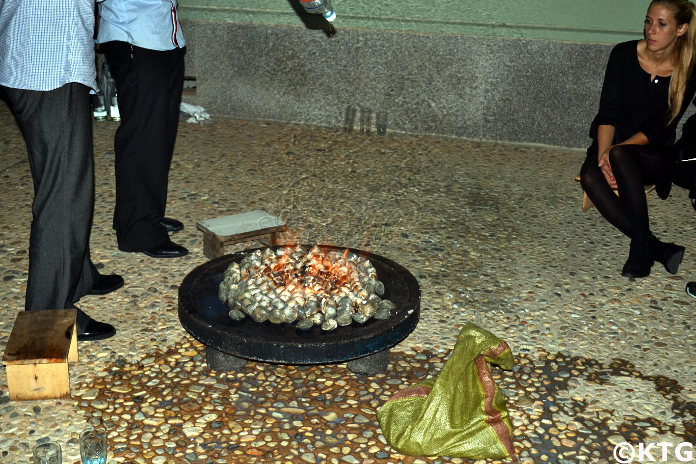 KTG traveller observes as our driver pours petrol on clams at the Nampo Ryonggang Hot Spa Hotel in Onchon county near Nampo city, North Korea (DPRK)