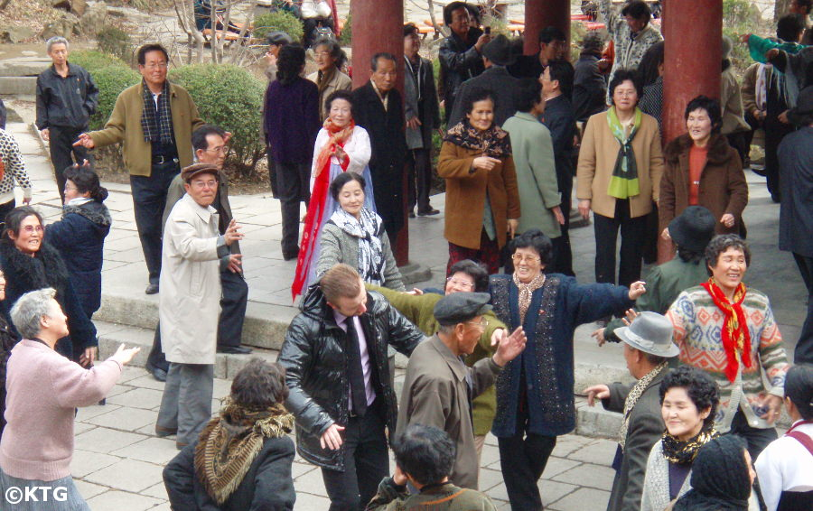 North Koreans dancing with a foreigner at Moran Park in Pyongyang
