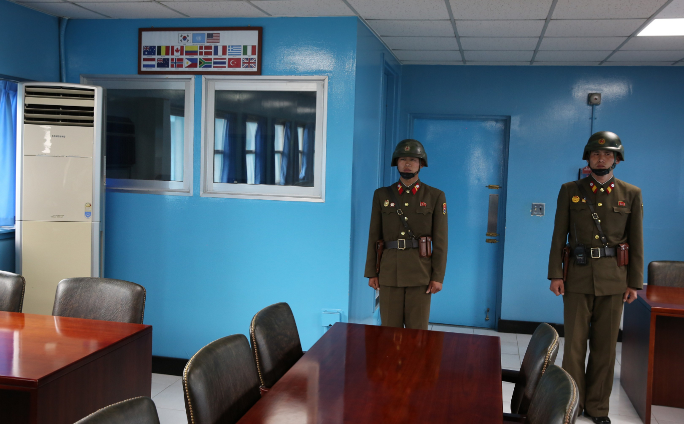 North Korean soldiers standing on the door of the blue negotiations room that leads to South Korea. It is strictly forbidden to go behind them. Trip arranged by KTG Tours