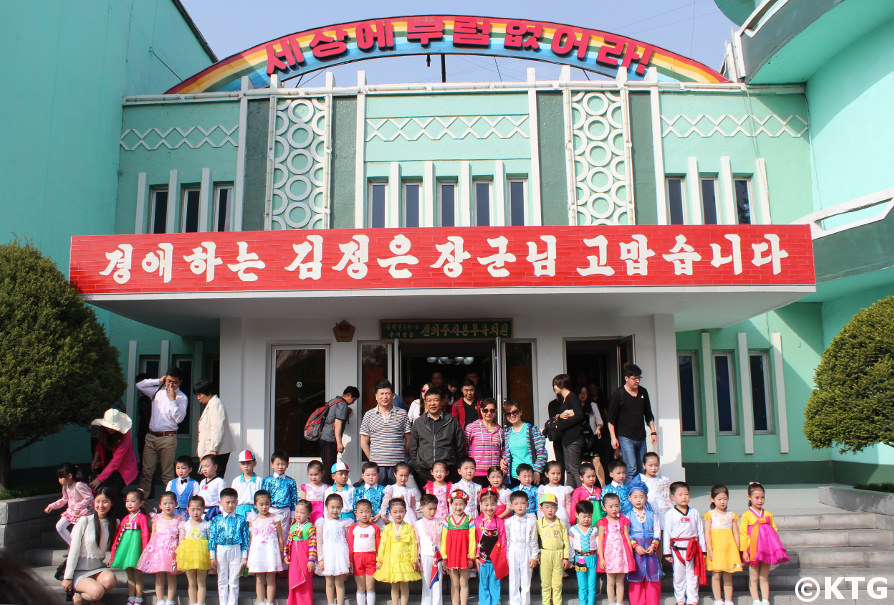 Chinese tourists pose with children at the Ponbu kindergarten in Sinuiju, North Pyongan Province, North Korea (DPRK). Tour arranged by KTG Tours
