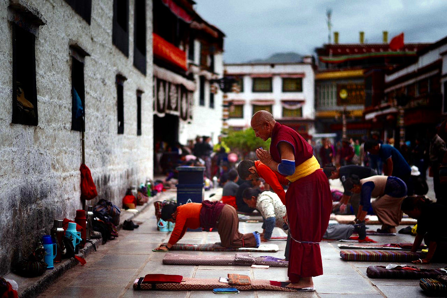Pilgrims praying by Jokhang temple in Lhasa, Tibet, China