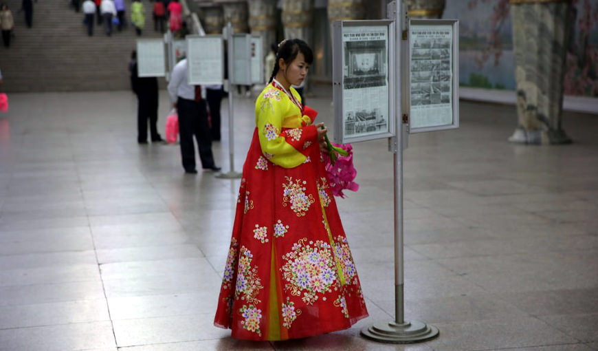 North Korean lady wearing a traditional Korean dress reading the newspaper at the Pyongyang metro