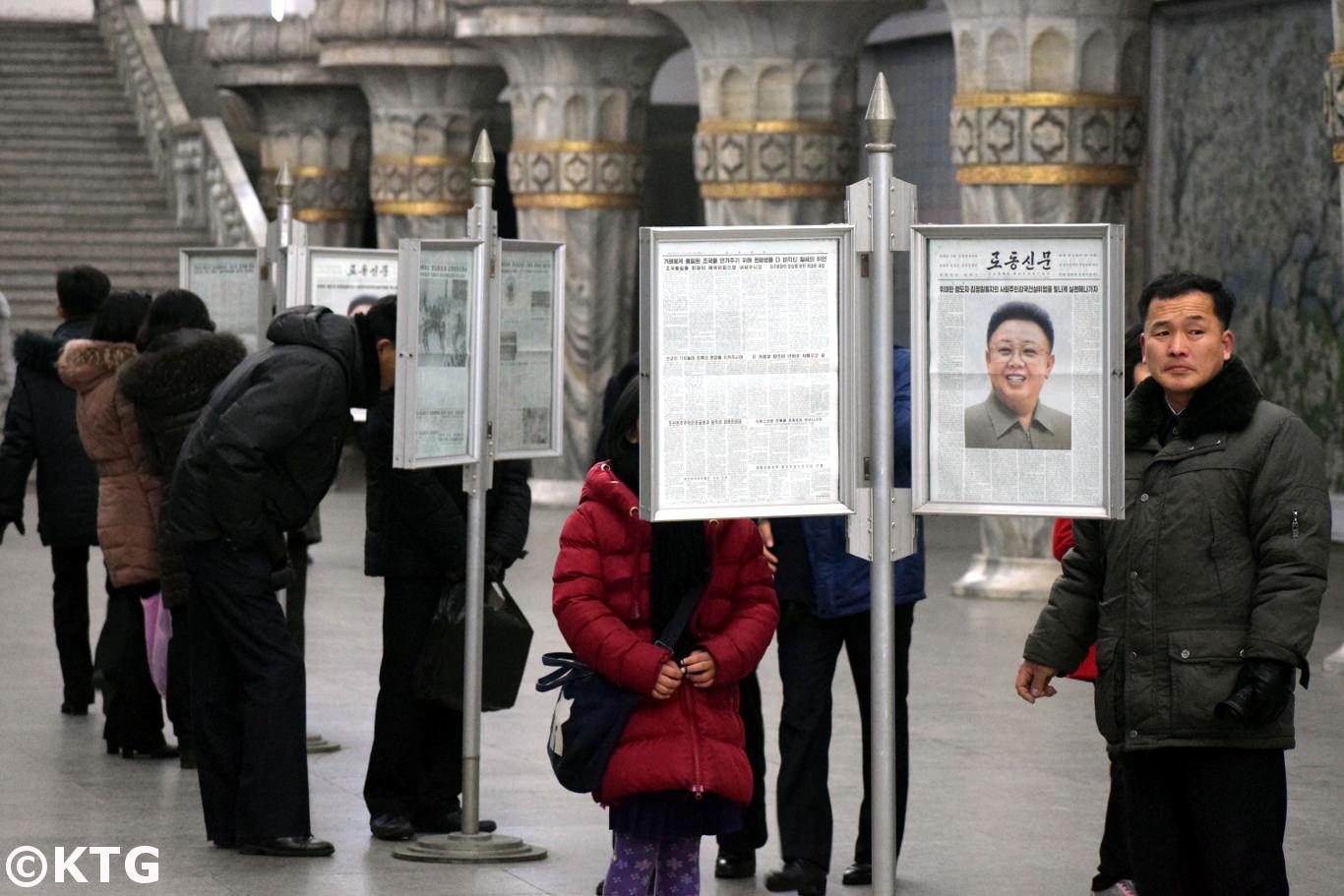 Transeúntes norcoreanos leyendo el periódico en la estación de metro. Foto tomada por viajes KTG