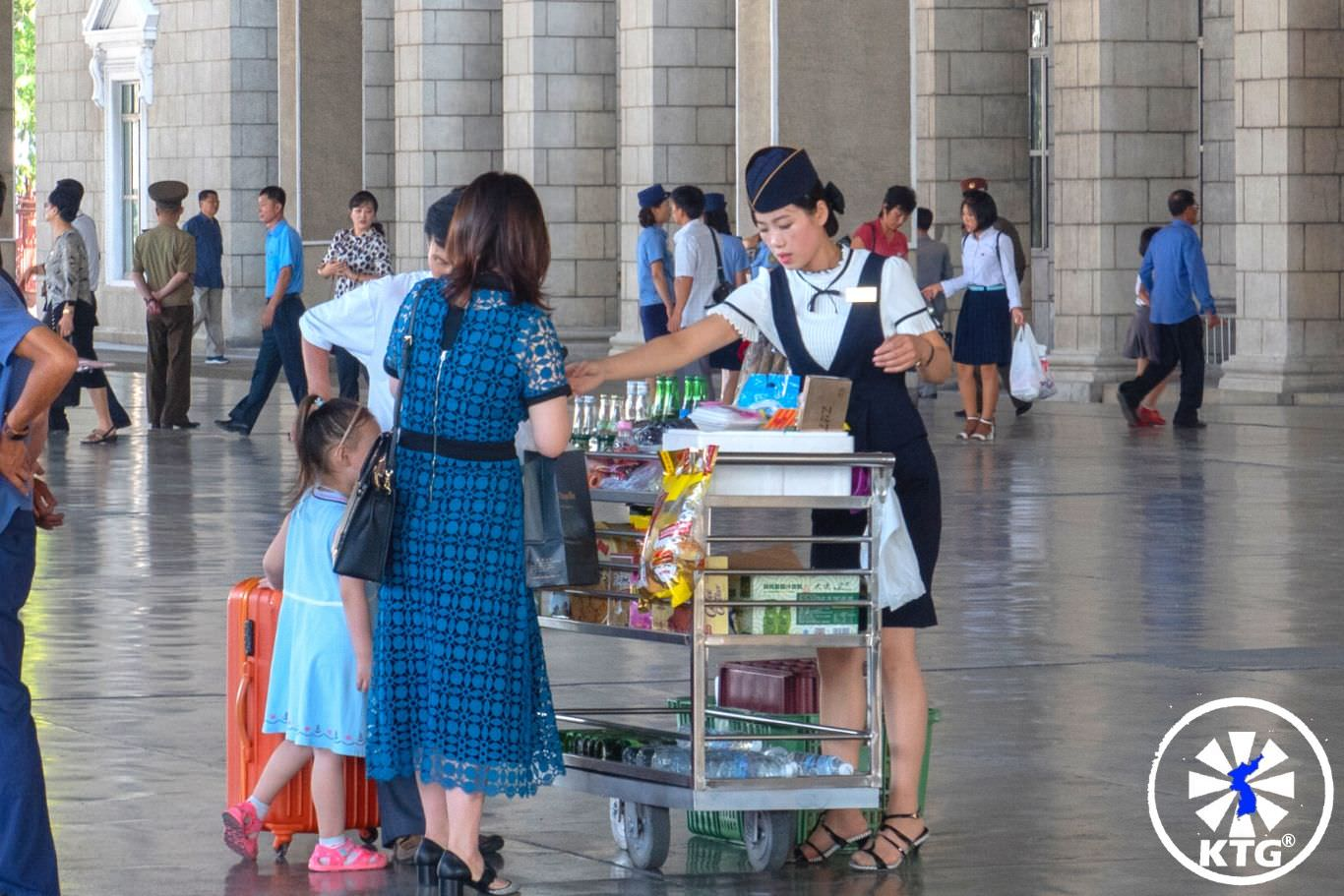 Lady selling snacks at the Pyongyang train station, North Korea (DPRK) before we take the train to China. Picture taken by KTG®