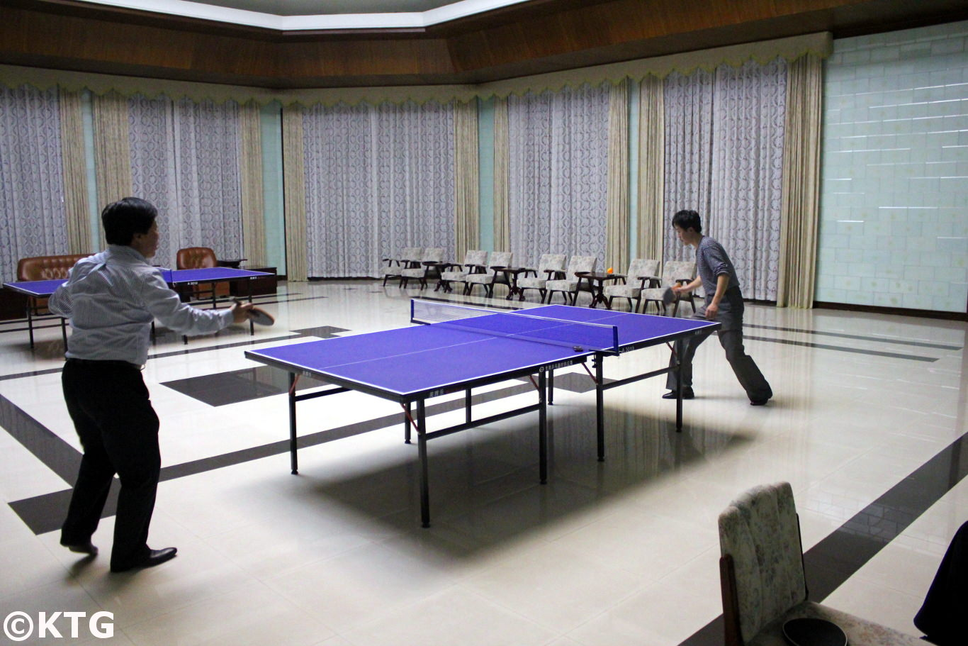 North Korean men playing table tennis at the Ryonggang Hot Spa Hotel near Nampo city in North Korea, DPRK. Picture taken by KTG Travel