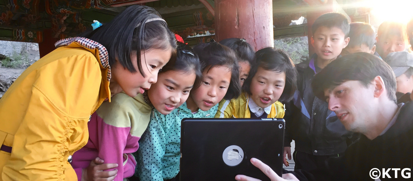 KTG staff member showing Korean children our DPRK 360 images