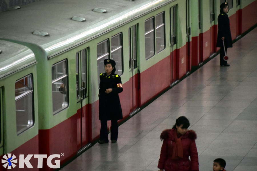 staff members of the Pyongyang metro, North Korea. Workers dress in military uniforms. Picture of North Korea taken by KTG Tours