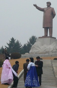 Newly married couple by the statue of Kim Il Sung in Mt. Dongbung, Hamhung, North Korea