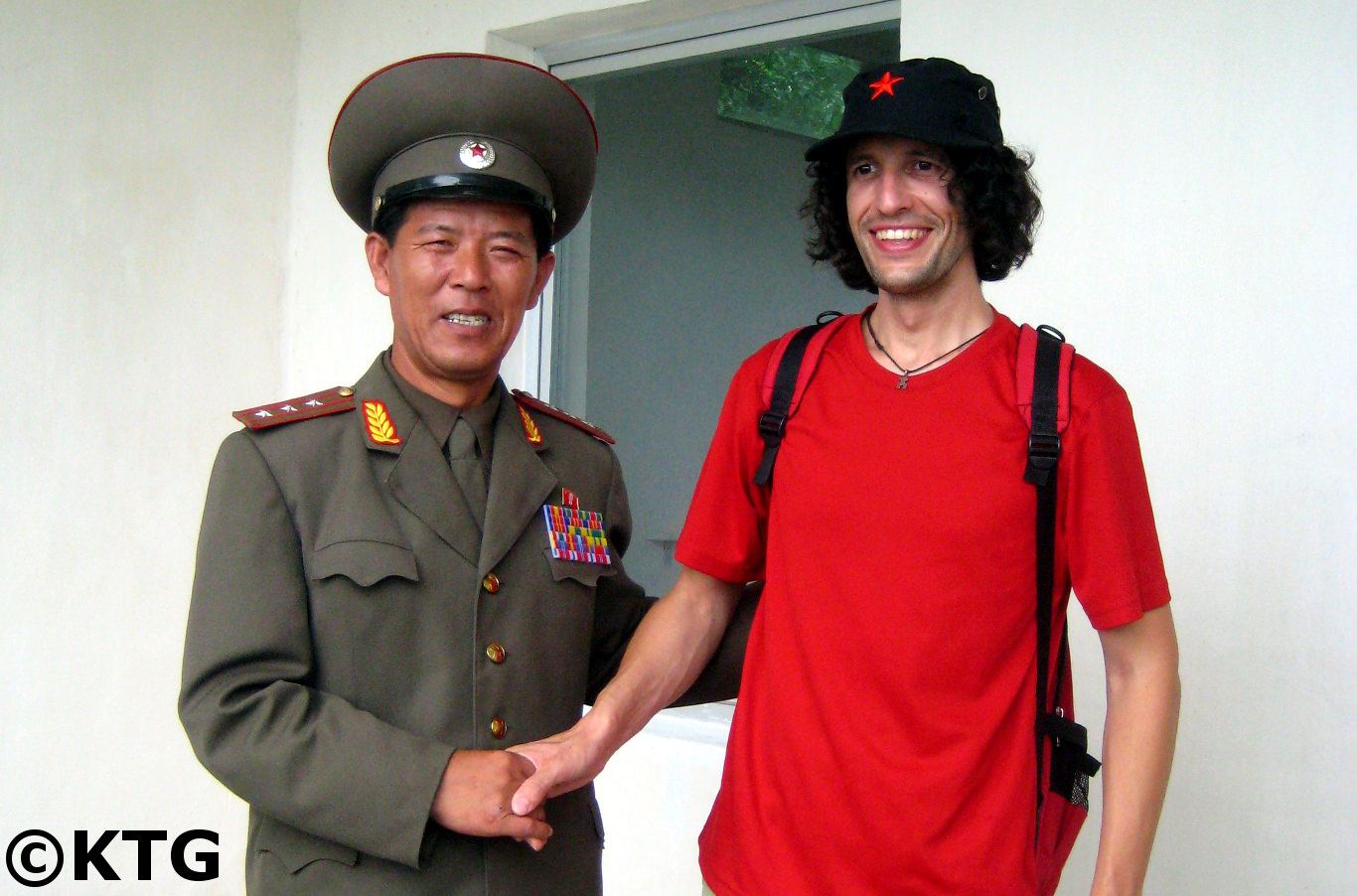 KTG traveller takes a picture with a North Koean Colonel. The (DPRK) North Korean military officer explains where South Korea have a concrete wall that strectches across the Korean peninsula