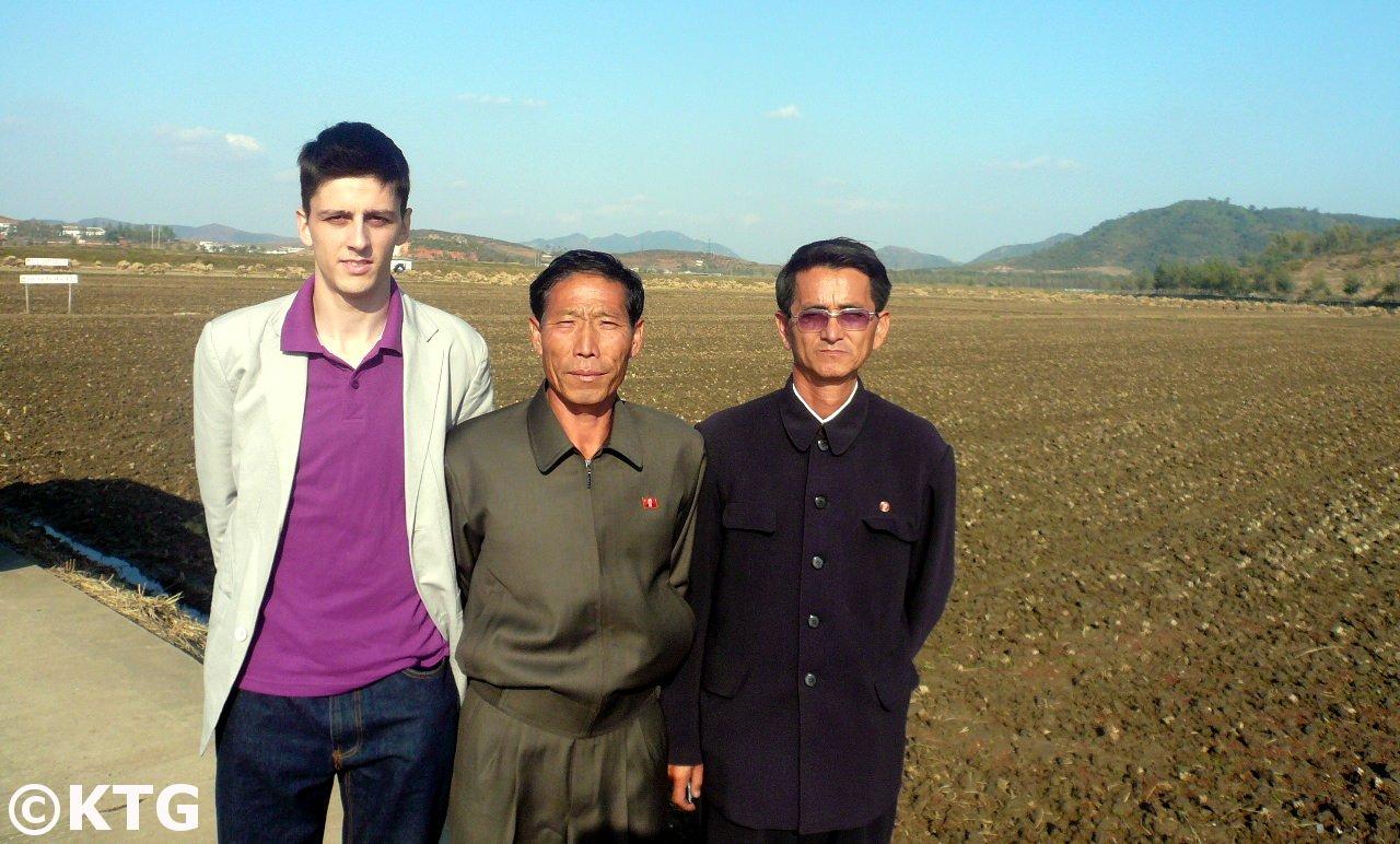 Miembro del equipo KTG posa con los encargados de la granja Chongsan cerca de la ciudad de Nampo en Corea del Norte