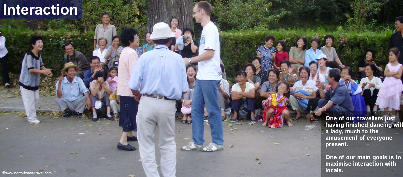 Personas of North Korea dancing with a traveller in the park