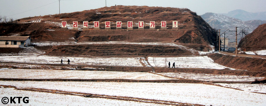 North Korean countryside in the winter with a giant slogan. Visit the DPRK with KTG Tours