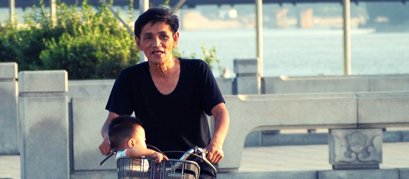 Grandfather in North Korea cycling with grandson. Tour arranged by KTG Travel