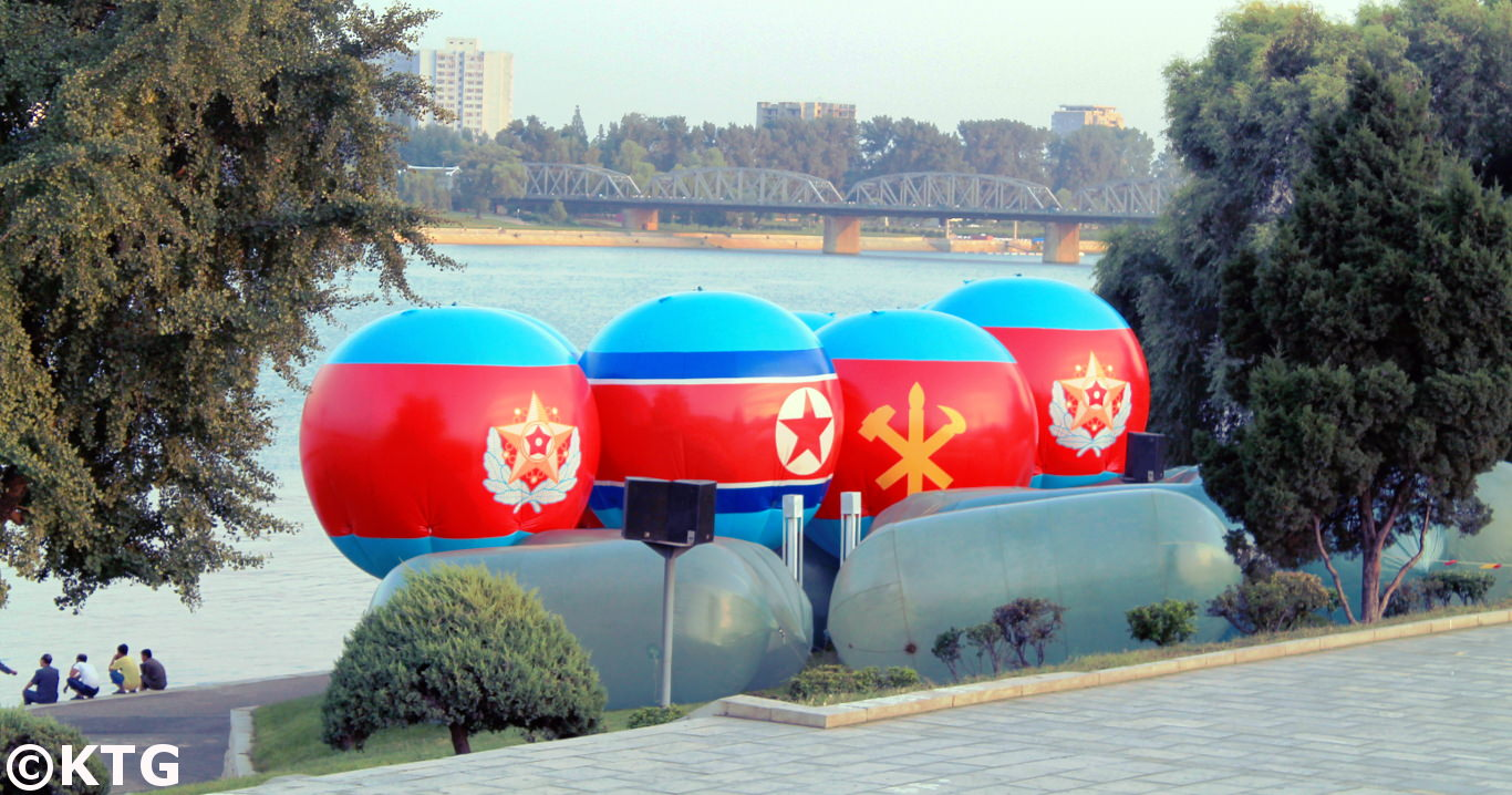 DPRK flag and the Korean Workers' Party emblem located in between two DPRK military emblems