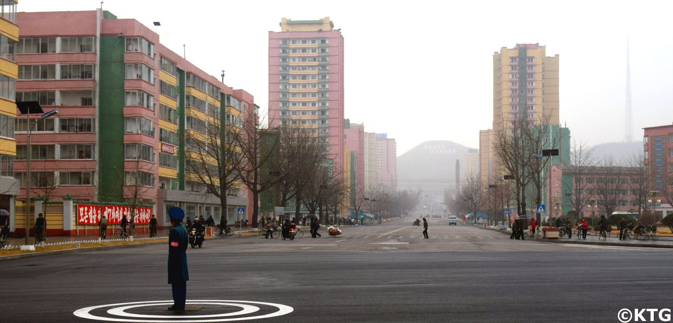 North Korean traffic police officer in Kaesong city centre, North Korea (DPRK). You can see the iconic high rise buildings in the background. Join KTG Tours to explore this historical city, home to no less than 12 UNESCO World Heritage sites