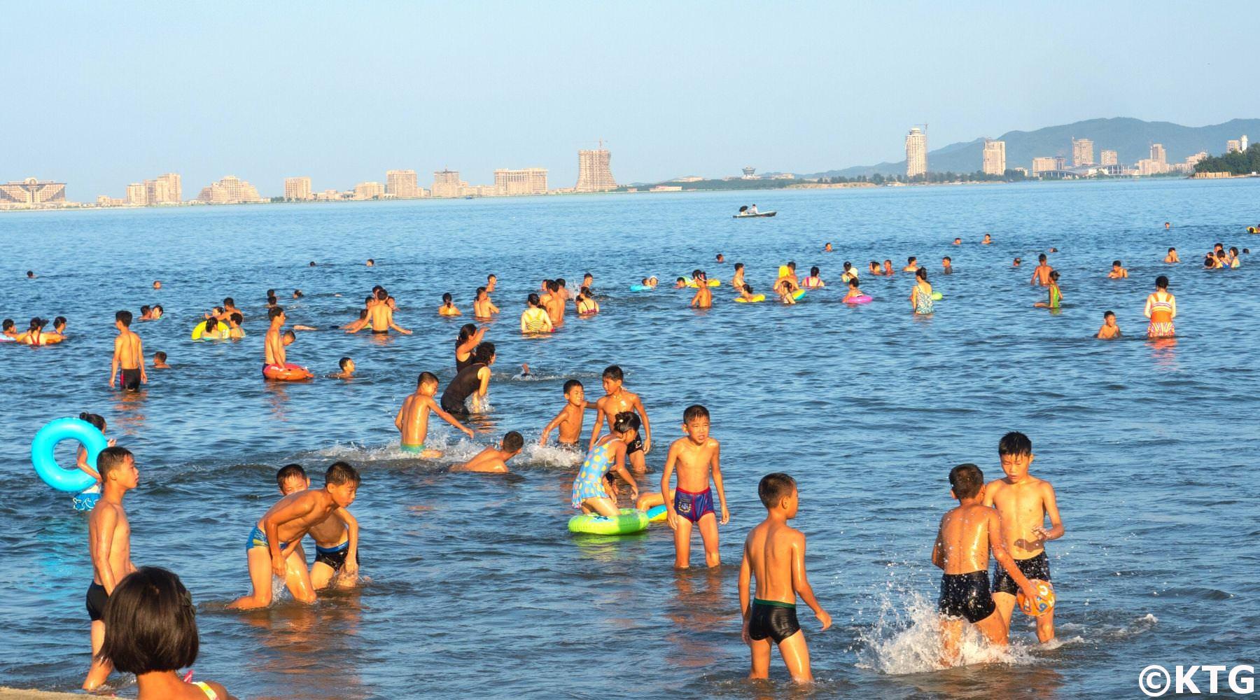 Niños divirtiéndose en la playa en Wonsan en Corea del Norte (RPDC). Puede ver el preyecto Wonsan-Kalma en el fondo de la imagen. Viaje organizado por KTG Tours