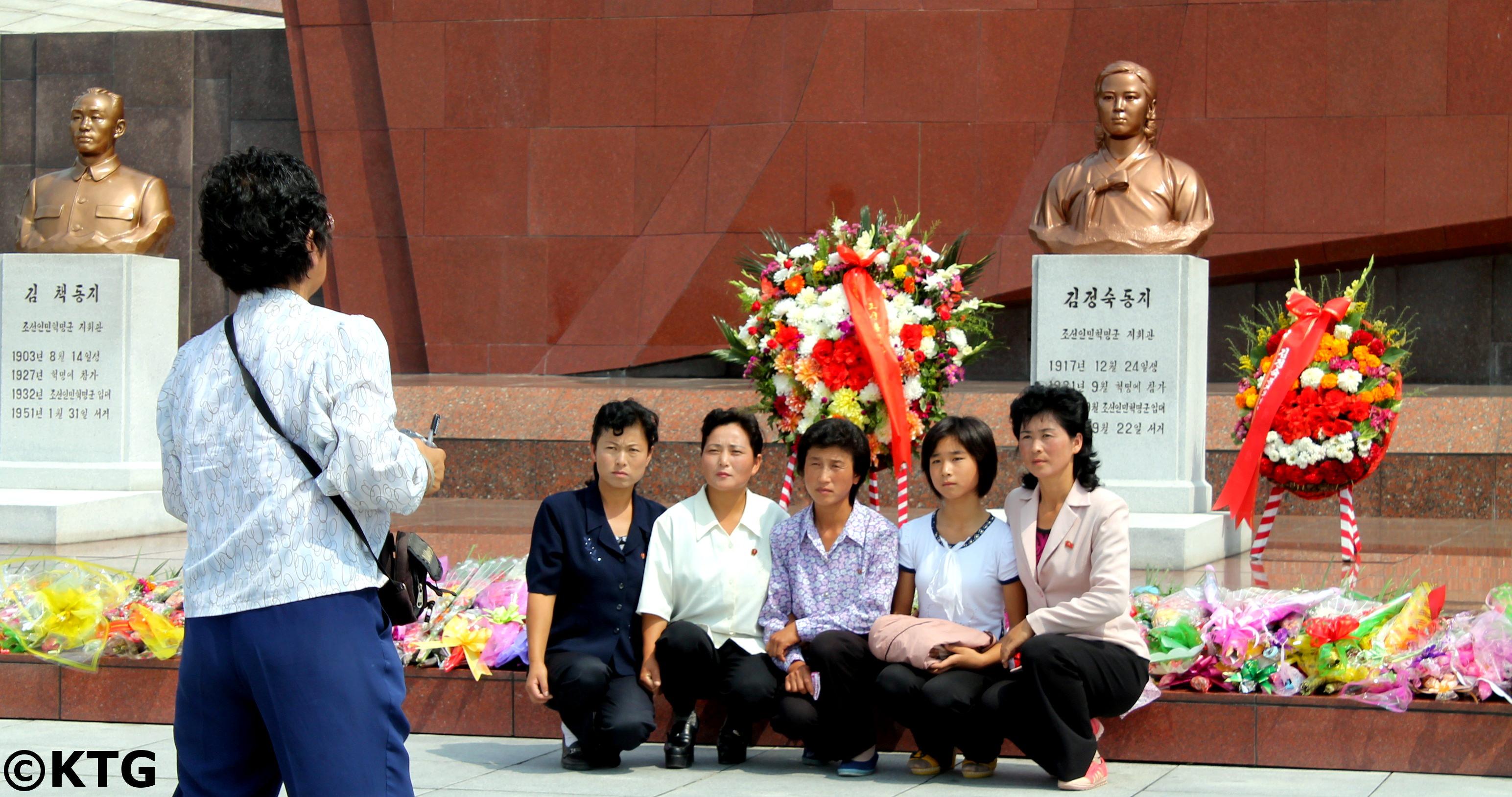 Una familia norcoreana se saca una foto en frente del busto de bronze de la Camarada Kim Jong Suk en el Cementerio de los Mártires Revolucionarios en Pyongyang en de Corea del Norte