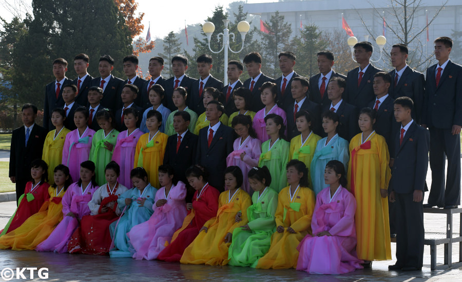 Group of Koreans taking a group picture at Kumsusan Memorial Palace in Pyongyang in North Korea. This is the most sacred place in the DPRK. As you can see they wear formal clothes. Ladies wear traditional Korean dresses and men wear suit and tie or mao suits. Picture taken by KTG Tours