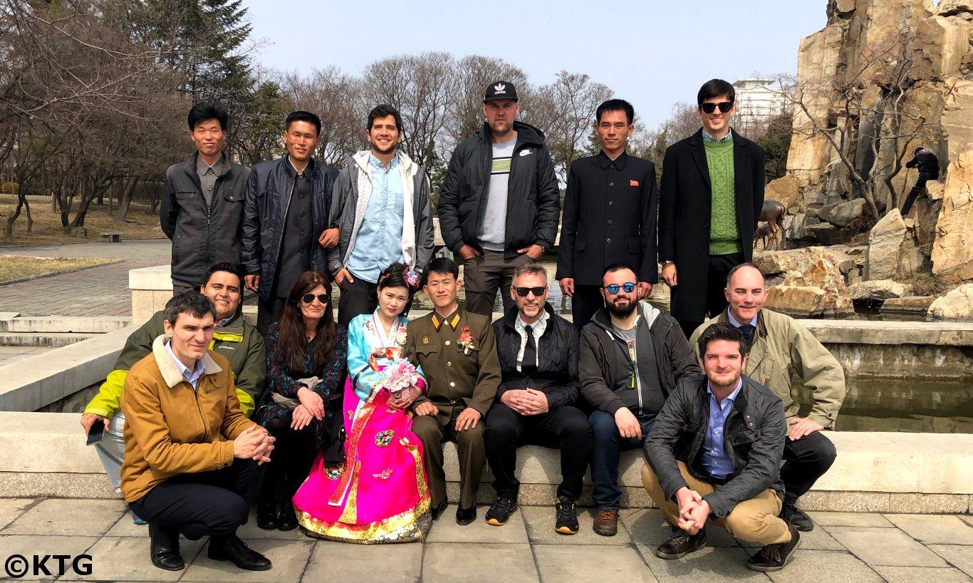 Pareja recién casada y un grupo de KTG tomando una foto juntos en el Parque de la Fuente en Pyongyang, la capital de la RPDC, es decir, Corea del Norte. Viaje organizado por KTG Tours