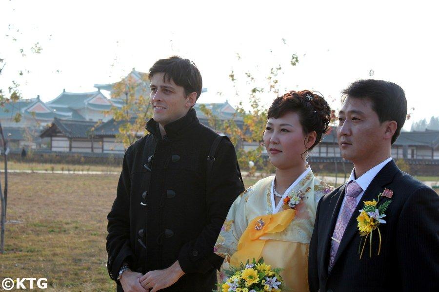 Un couple récemment marié et un membre du personnel de KTG prenant une photo ensemble dans ce qui était autrefois connu sous le nom de mini-Pyongyang à Pyongyang, la capitale de la RPDC, c'est-à-dire la Corée du Nord. Voyage organisé par KTG Tours