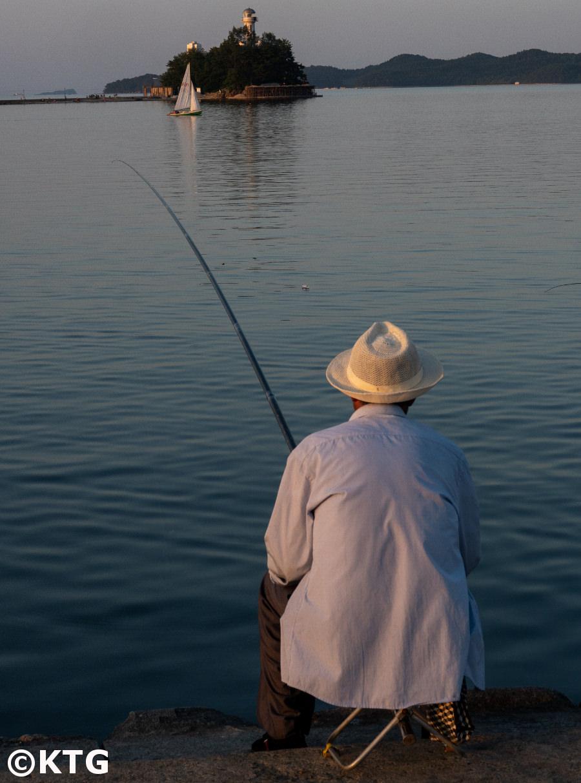 Hombre pescando en la ciudad de Wonsan, provincia de Kangwon, Corea del Norte (RPDC). Puedes ver el islote Jangdok en el fondo. Viaje organizado por KTG Tours