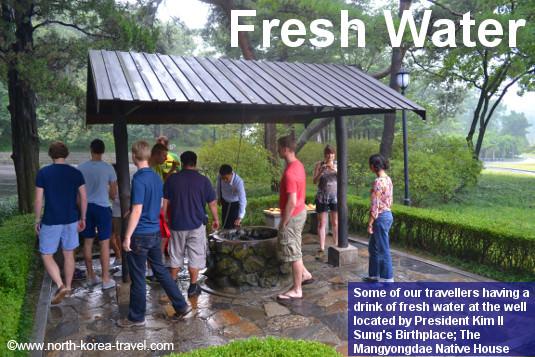 Nuestro viajeros tomando agua del pozo en Mangyongdae, el lugar de nacimiento del Presidente Eterno de Corea del Norte, Kim Il Sung